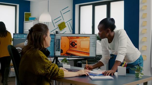 Multiethnische frauenspieldesigner, die computer betrachten