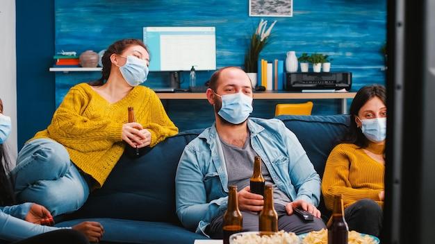 Multiethnische freunde, die beim fernsehen lachen, sitzen auf dem sofa und trinken bier mit gesichtsmaske während des ausbruchs der covid-pandemie als prävention gegen die verbreitung von viren