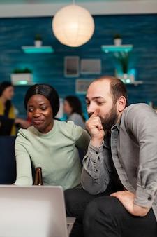 Multiethnische freunde, die freundschaften feiern und sich lustige videos auf dem laptop ansehen, der auf der couch sitzt. im hintergrund verbringen zwei frauen, die bier trinken, die zeit zusammen während der unterhaltungsparty.