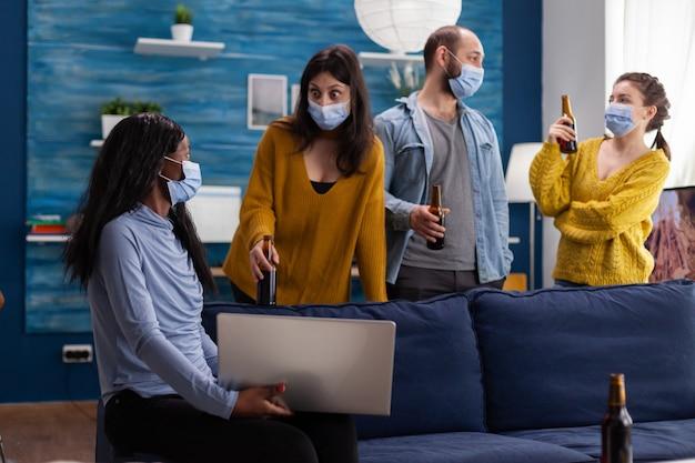Multiethnische freunde, die gesichtsmaske tragen und bier mit laptop trinken, halten soziale distanz, um die ausbreitung von coronavirus während der globalen pandemie zu verhindern und spaß im wohnzimmer zu haben. konzeptionelles bild.