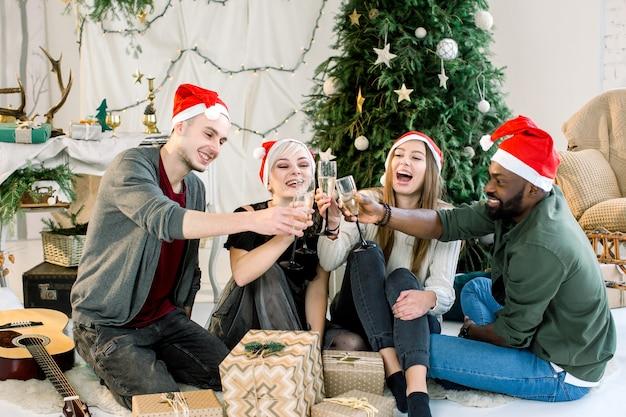 Multiethnische freunde feiern neujahr und rösten mit gläsern champagner