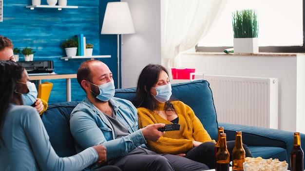 Multiethnische freunde lachen beim anschauen von filmen im fernsehen und haben viel spaß beim sitzen auf dem sofa im wohnzimmer mit gesichtsmaske während des ausbruchs des coronavirus, die soziale distanzierung respektieren und bier und chips genießen