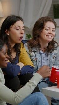 Multiethnische freunde sitzen auf der couch und haben ein online-videoanruf-treffen mit virtuellen kollegen mit laptop using