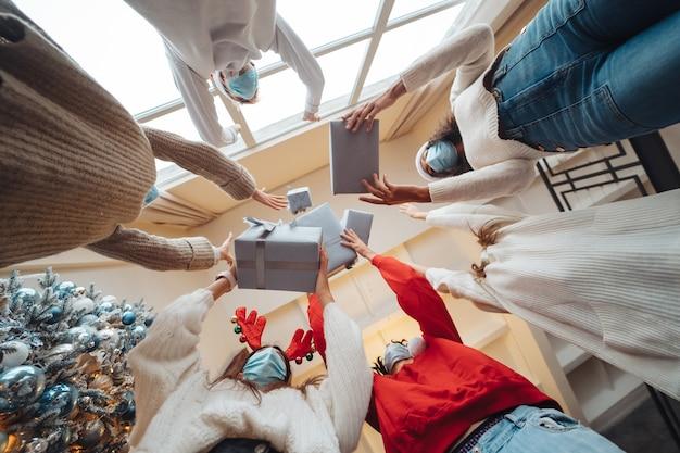 Multiethnische freunde werfen ihre weihnachtsgeschenke in die luft.