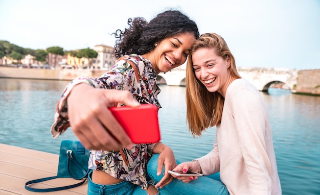 Multiethnische freundinnen, die zusammen selfie im stadtpark nehmen