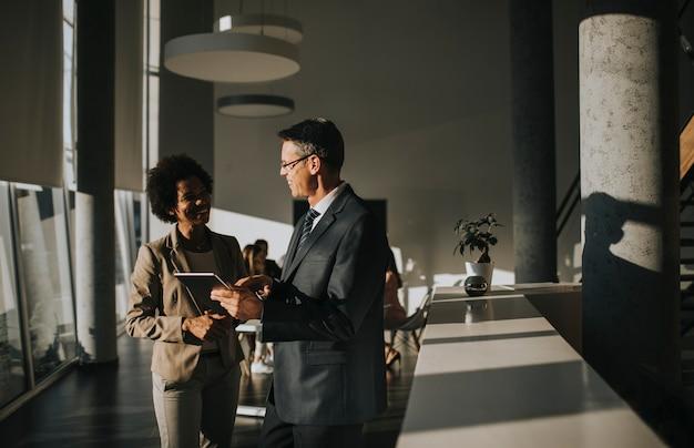 Multiethnische geschäftsleute, die digitales tablet verwenden, während sie im büro stehen