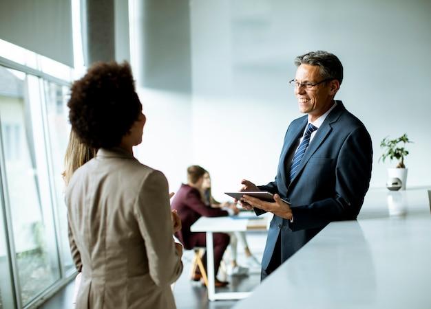 Multiethnische geschäftsleute, die digitales tablet verwenden, während sie im modernen büro stehen