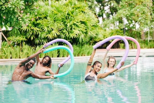 Multiethnische glückliche junge leute, die mit schwimmenden nudeln im schwimmbad des kurhotels trainieren