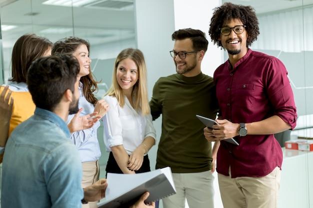 Multiethnische gruppe junge leute, die im modernen büro und im brainstorming stehen