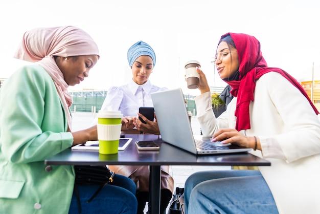 Multiethnische gruppe muslimischer mädchen, die freizeitkleidung und traditionelle hijab-bindung im freien tragen