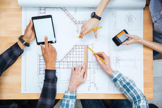 Multiethnische gruppe von designern, die berechnungen anstellen und mit blaupausen mit tablet und smartphone arbeiten