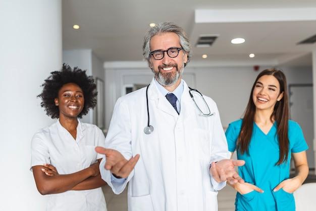 Multiethnische gruppe von drei ärzten und krankenschwestern, die in einem krankenhauskorridor stehen und peelings und mäntel tragen.