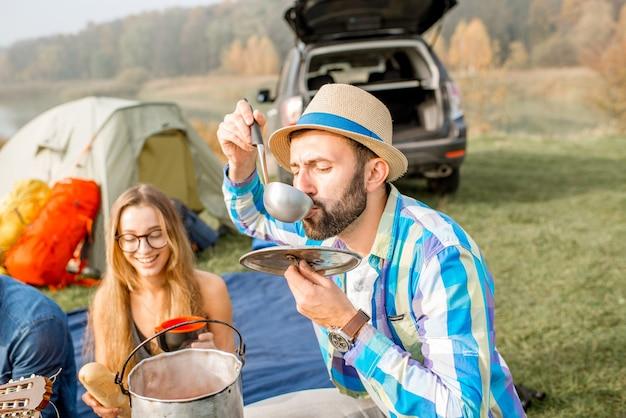 Multiethnische gruppe von freunden, die lässig gekleidet ein picknick machen, suppe mit kessel kochen während der erholung im freien mit zelt, auto und wanderausrüstung in der nähe des sees