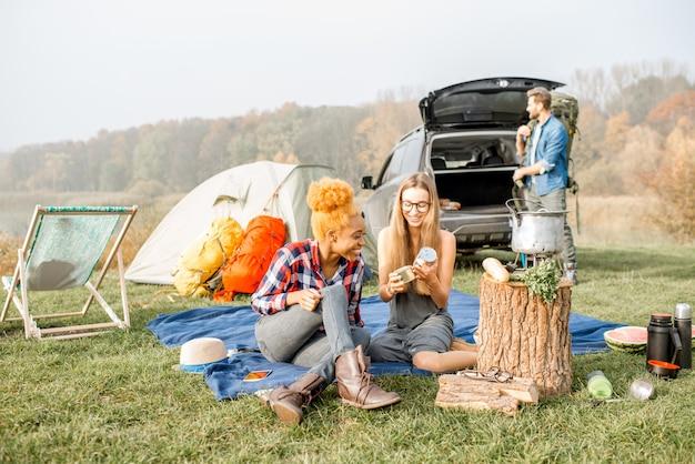 Multiethnische gruppe von freunden, die lässig gekleidet ein picknick während der erholung im freien mit zelt, auto und wanderausrüstung in der nähe des sees machen