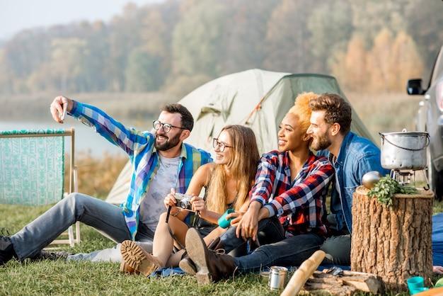 Multiethnische gruppe von freunden, die lässig gekleidet sind und spaß haben, während der erholung im freien mit zelt, auto und wanderausrüstung in der nähe des sees zusammen ein selfie-foto zu machen
