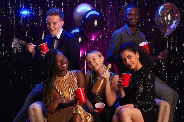 Multiethnische gruppe von jungen leuten, die rote tassen halten, während sie geburtstagsfeier oder abschlussballnacht genießen, kopieren raum