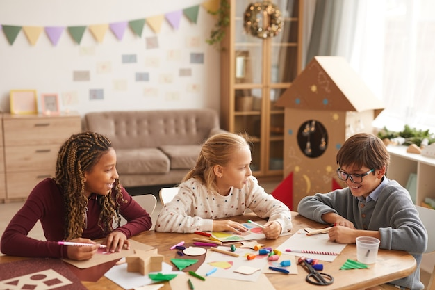 Multiethnische gruppe von kindern, die bilder zusammen zeichnen, während sie kunst- und handwerksunterricht genießen, raum kopieren