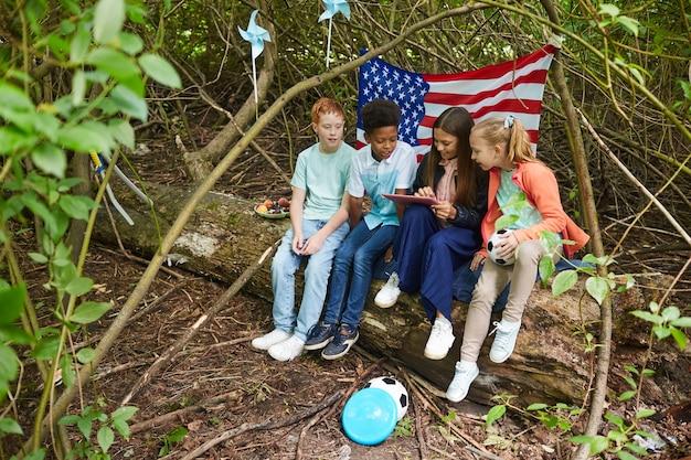 Multiethnische gruppe von kindern, die digitales tablett verwenden, während sie im hof spielen, der sich unter büschen mit amerikanischer flagge versteckt