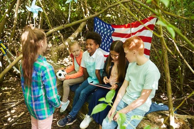 Multiethnische gruppe von kindern, die sich unter zweigen eines großen baumes verstecken, während sie im wald oder im hinterhof spielen