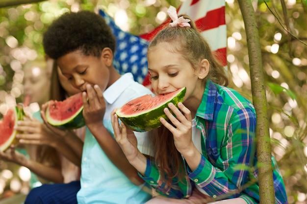 Multiethnische gruppe von kindern, die wassermelone essen, die in reihe sitzen, während im sommer draußen spielen