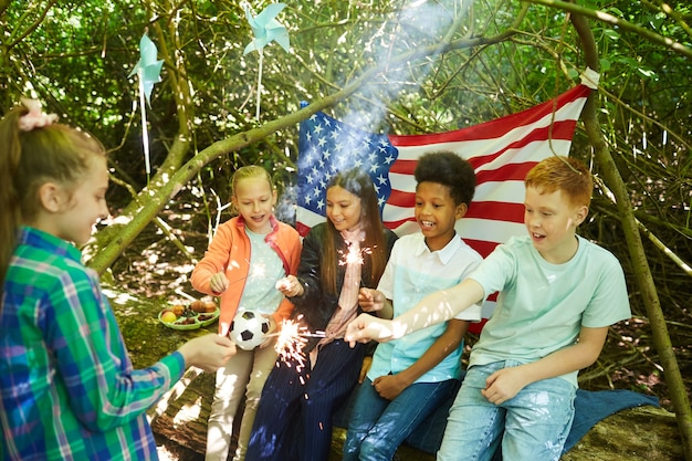 Multiethnische gruppe von kindern, die wunderkerzen anzünden, während sie sich unter zweigen eines großen baumes im wald verstecken oder im hinterhof spielen