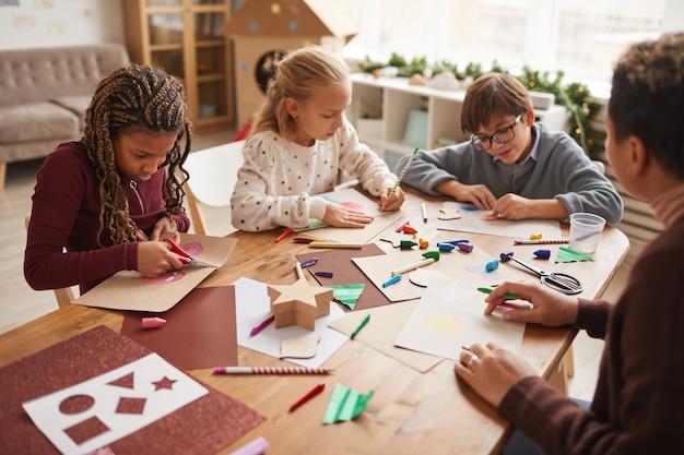 Multiethnische gruppe von kindern, die zusammen handgemachte weihnachtskarten machen, während sie kunst- und handwerksunterricht genießen, raum kopieren