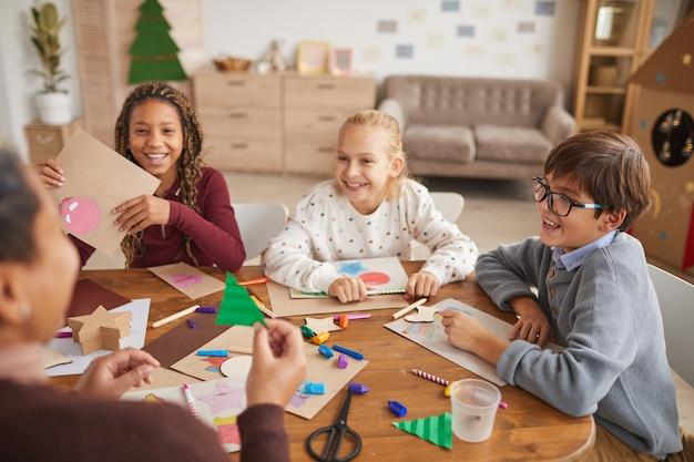 Multiethnische gruppe von lächelnden kindern, die bilder zusammen zeichnen, während kunst- und handwerksklasse genießen, raum kopieren