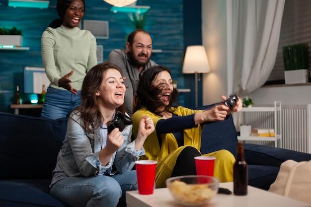 Multiethnische gruppe von menschen, die bei videospielen gewinnen und spaß haben. gruppe von freunden gemischter rassen, die spiele spielen, während sie spät in der nacht auf dem sofa im wohnzimmer sitzen.