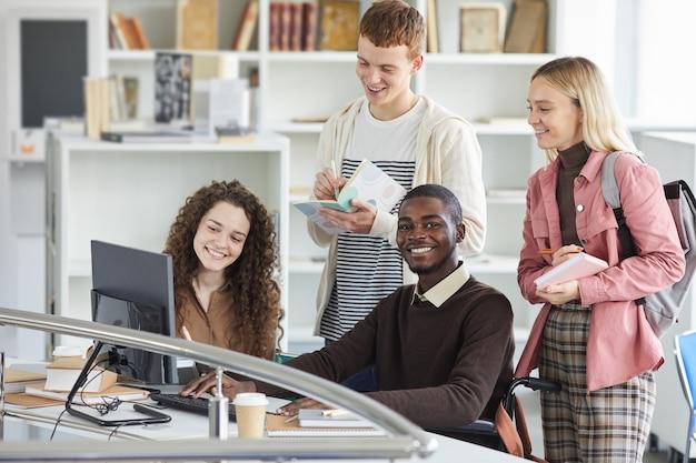 Multiethnische gruppe von studenten, die telekommunikationsgeräte während des studiums in der universitätsbibliothek verwenden, konzentrieren sich auf afroamerikanischen mann, der in die kamera lächelt,