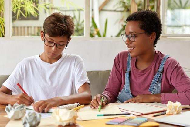 Multiethnische gruppenmitglieder schreiben einen gemeinsamen aufsatz, sitzen mit papieren und notizblock in freizeitkleidung am tisch. asiatischer junge erhält beratung von einem dunkelhäutigen freund, überprüfen sie informationen aus dokumenten