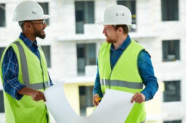Multiethnische ingenieure diskutieren bauprojekt