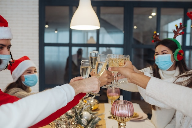 Multiethnische junge leute, die silvester feiern, stoßen an, gemischtrassige freunde, die spaß an der partyfeier haben und gratulieren, champagner zu trinken