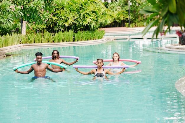 Multiethnische junge leute, die wassergymnastik mit schwimmenden nudeln im schwimmbad des hotels tun