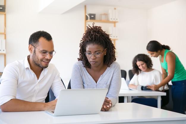 Multiethnische kollegen, die laptopschirm betrachten