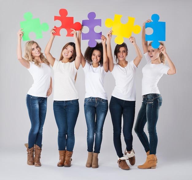 Multiethnische mädchen mit farbigem puzzle