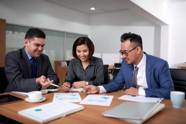 Multiethnische männliche und weibliche kollegen, die im büro sitzen und diagramme bei der sitzung besprechen