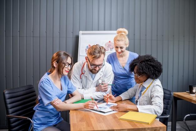 Multiethnische mediziner diskutieren während der konferenz mit dokumenten am tisch im modernen büro
