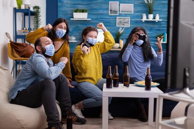 Multiethnische menschen feiern den sieg des videospiels im wohnzimmer mit joystick, der eine gesichtsmaske trägt und in zeiten des corona-ausbruchs soziale distanz hält. diverse freunde, die bier und pommes genießen.