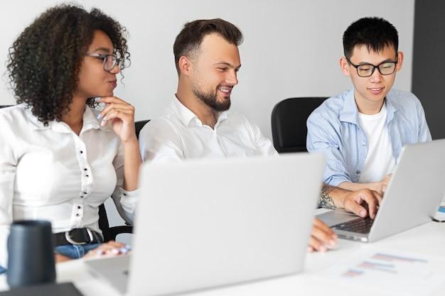 Multiethnische menschen lächeln und denken über ideen für ein startup-projekt nach, während sie am tisch sitzen und einen laptop im modernen büro verwenden