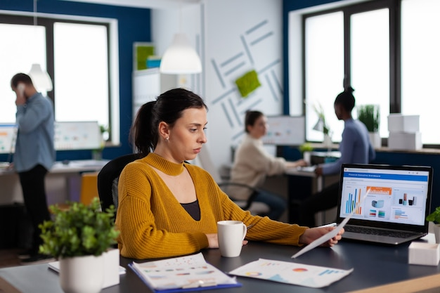 Multiethnische menschen von start-up-unternehmen analysieren finanzdiagramme mit dokumenten