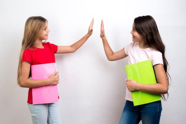 Multiethnische schulmädchen geben high-five