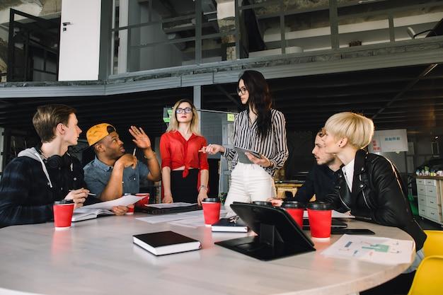 Multiethnische verschiedene gruppe glückliche kollegen, die zusammenarbeiten. kreativteam, zufälliger geschäftsmitarbeiter oder studenten in der projektbesprechung im modernen büro. startup oder teamwork-konzept