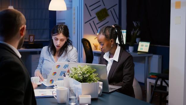 Multiethnische, vielfältige geschäftsleute, die spät in der nacht bei der management-präsentation im büro-konferenzraum brainstorming-unternehmensideen arbeiten. manager mit dunkler hautfarbe schreibt unternehmensstatistiken auf laptop