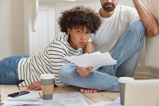 Multiethnische weibliche und männliche geschäftskollegen denken über finanzberichte nach