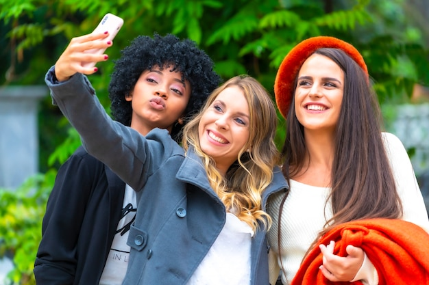 Multiethnischer lebensstil von drei freundinnen, die ein selfie-foto in der stadt machen