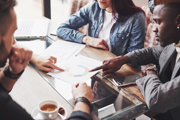 Multiethnischer unternehmer, kleinunternehmenskonzept. frau, die kollegen etwas auf laptop-computer zeigt, während sie sich um einen konferenztisch versammeln