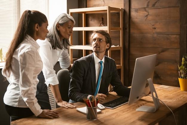Multiethnisches business-team von jungen leuten, die während eines unternehmenstreffens an einem projekt arbeiten. verschiedene mitarbeiter teilen ihre ideen mit kollegen. teamwork-konzept.
