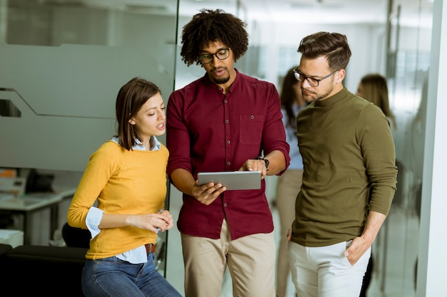Multiethnisches geschäftsteam, das eine digitale tablette im büro der kleinen startfirma verwendet
