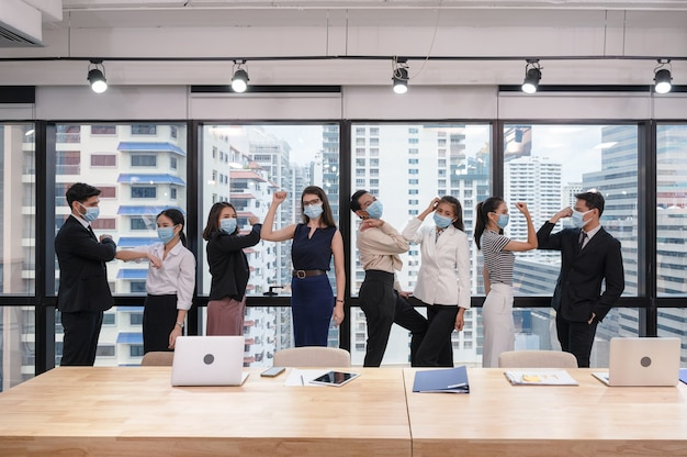 Multiethnisches geschäftsteam, das gesichtsmaskengruß mit ellbogenstoß in neuem normalem büro am geschäftsviertel trägt