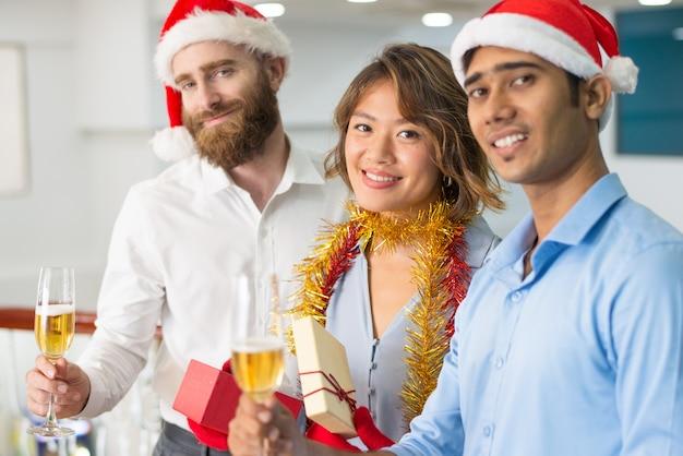 Multiethnisches geschäftsteam, das weihnachten champagne trinkt